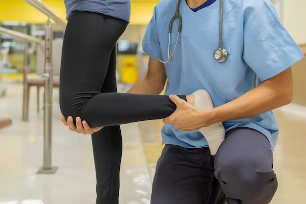Los médicos de sexo masculino están ayudando a pacientes femeninos a hacer ejercicio en el gimnasio