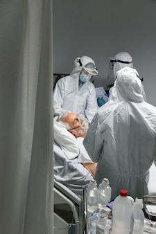 Médicos de tiro medio y paciente con máscara de oxígeno.