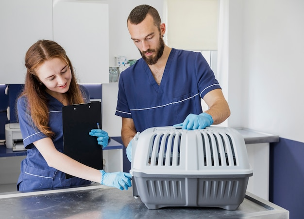 Médicos de tiro medio con portapapeles y jaula para gatos