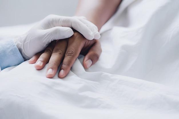 Los médicos usan guantes médicos tomados de la mano del hombre paciente con amor, cuidado, ayuda, aliento y empatía en la sala del hospital de enfermería.