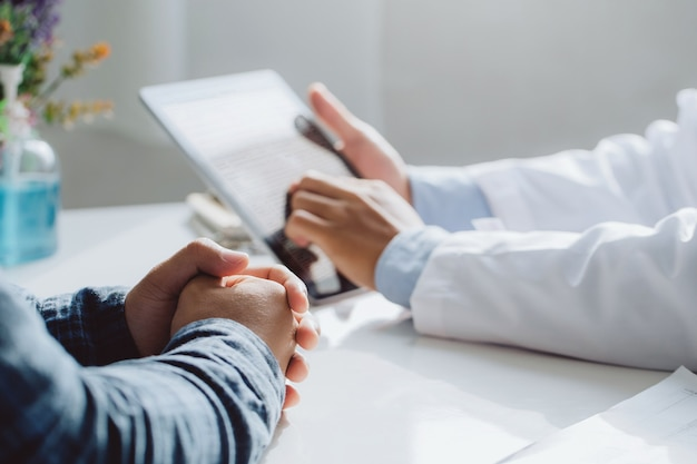 Médicos varones sosteniendo tableta digital mientras discuten y consultan al paciente.concepto de atención médica y medicina. doctor y paciente