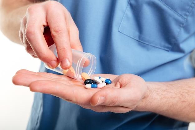 Médicos varones vertiendo píldoras de una botella en su palma