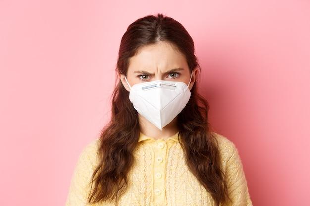 Medidas preventivas, concepto de atención médica. cerca de mujer enojada en respirador frunciendo el ceño, mirando con cara de juicio a la persona sin máscara, de pie contra la pared rosa.