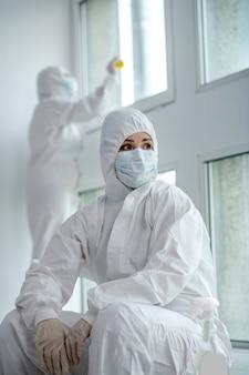 Medidas de protección. trabajadora médica rubia cansada con ropa protectora y máscara médica sentada junto a la ventana, sus colegas desinfectan los paneles