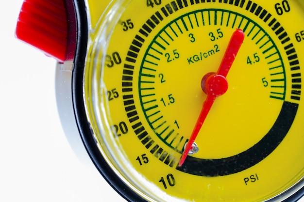 Medidor de presión de neumáticos para el coche en el fondo blanco