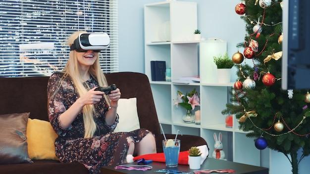Medio cerca de buena mujer jugando un juego con joystick en gafas de realidad virtual