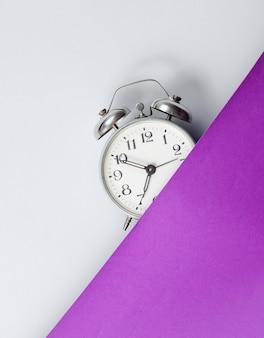 Medio despertador en mesa de color gris púrpura. estilo retro de los 80. vista superior