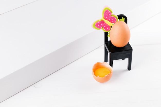 Medio huevo crudo con yema sobre una mesa blanca y un huevo está sentado en una silla negra con decoración de flores de pascua. idea mínima del concepto de pascua, enfoque selectivo