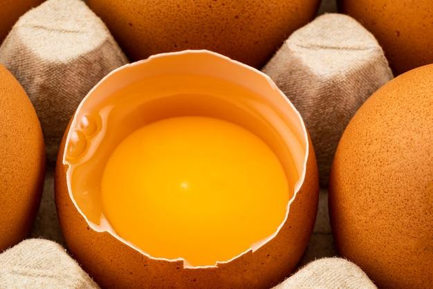 Medio huevo de gallina roto y huevos de gallina marrón en cartón de huevos.