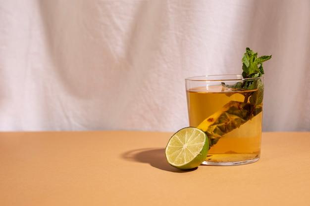 Medio limón con bebida de cóctel dispuesto en el escritorio marrón delante de la cortina blanca
