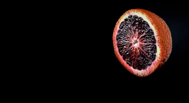 Medio naranja rojo siciliano maduro jugoso en la oscuridad