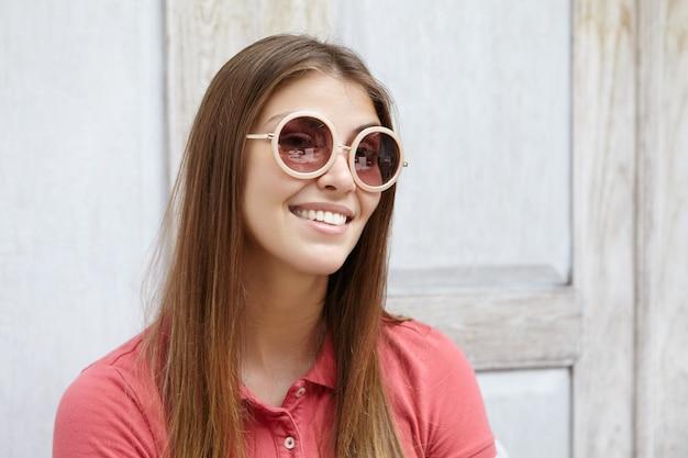 Medio perfil de atractiva joven mujer caucásica con pelo largo y liso vestida con camisa de polo a través de lentes de espejo de sus elegantes gafas de sol redondas y sonriendo alegre