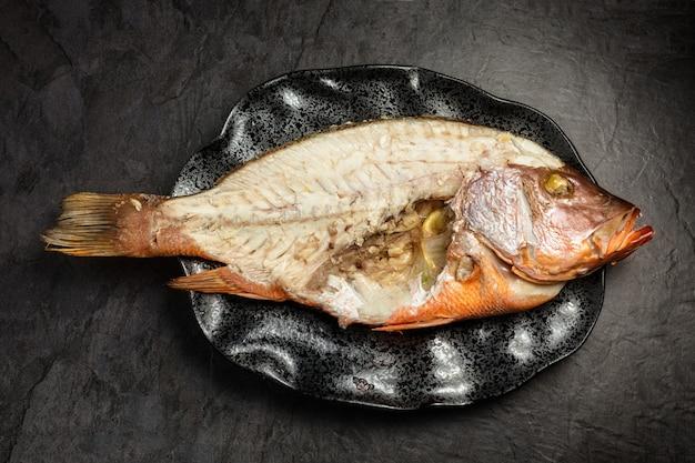 Medio pescado pargo rojo con espinas expuestas