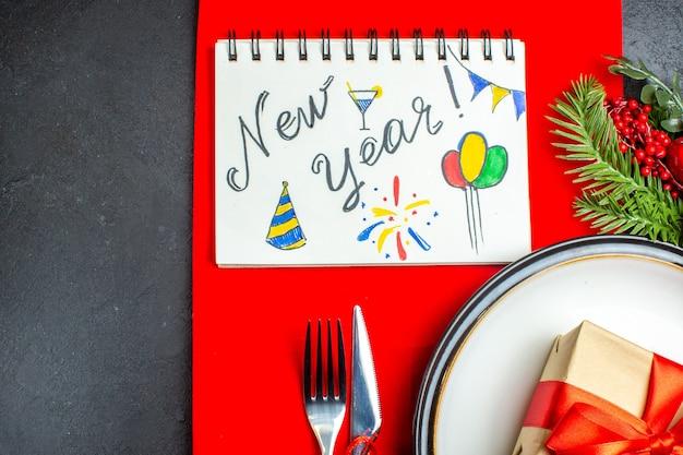Medio plano de platos de cena con regalo y ramas de abeto cubiertos juego de accesorios de decoración cono de coníferas siguiente cuaderno con escritura de año nuevo y dibujos en una servilleta roja