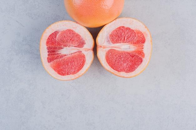 Medio pomelo cortado y entero sobre fondo gris.
