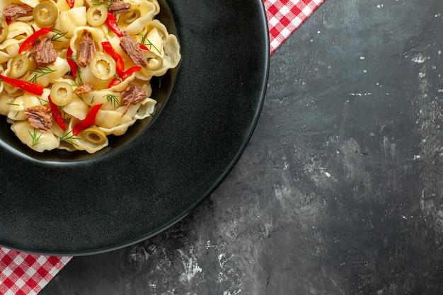 Medio tiro de deliciosa conchiglie con verduras en un plato negro y un cuchillo sobre una toalla despojada de rojo sobre la mesa gris