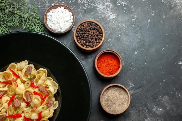 Medio tiro de deliciosa conchiglie con verduras y verduras en un plato y cuchillo y diferentes especias sobre fondo gris