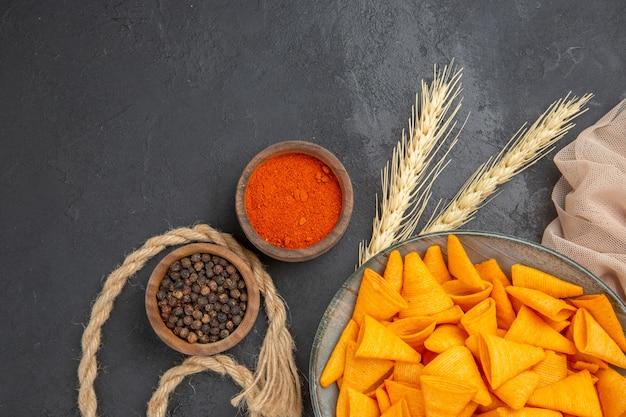 Medio tiro de deliciosas patatas fritas caídas botellas pimientos sobre una toalla y cuerda sobre un fondo negro
