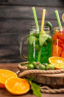 Medio tiro de deliciosos jugos y frutas frescas en una bandeja de madera sobre un fondo marrón