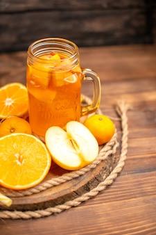 Medio tiro de jugo fresco orgánico en una botella y vaso servido con tubo y frutas sobre una tabla de cortar y sobre una mesa de madera marrón