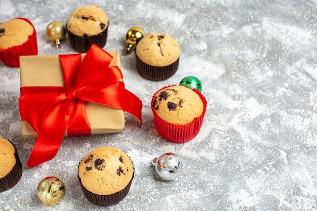 Medio tiro de regalo con cinta roja entre deliciosos cupcakes pequeños recién horneados y accesorios de decoración en la mesa de hielo