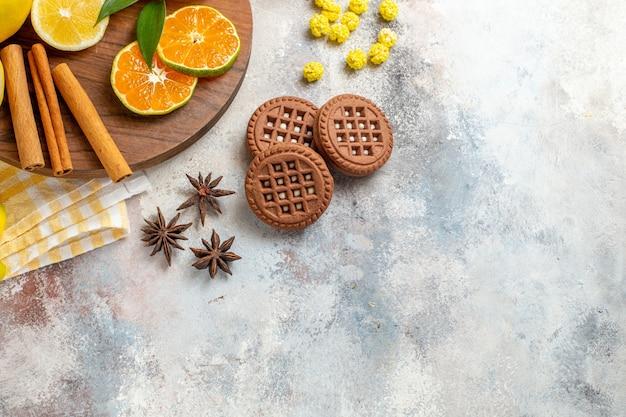 Medio tiro de rodajas de limón canela lima sobre una tabla de cortar de madera y galletas en el cuadro blanco