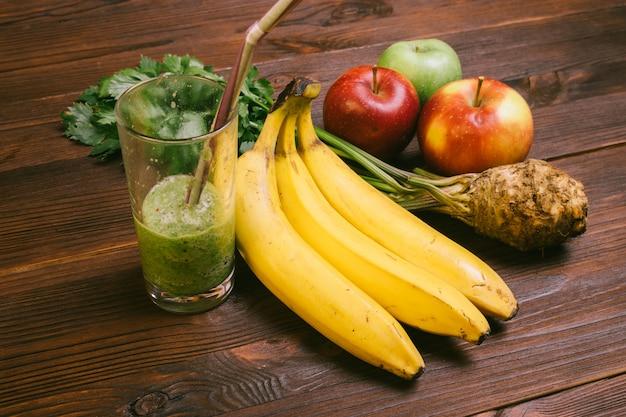 Medio vaso lleno de batido con paja, plátano, raíz de apio y manzanas en una mesa de madera oscura