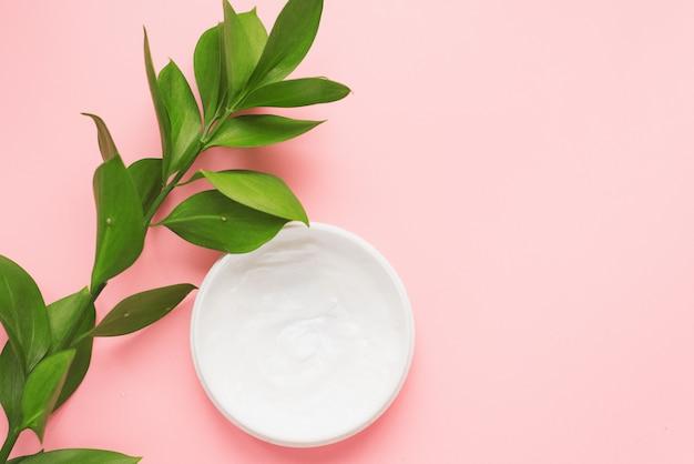 Medios para el cuidado de la piel, rejuvenecimiento e hidratación de la cara. crema hidratante sobre un fondo rosa patel con una rama verde