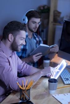 Medios de entretenimiento. hombre encantado positivo alegre mirando la pantalla de la tableta y riendo mientras se divierte