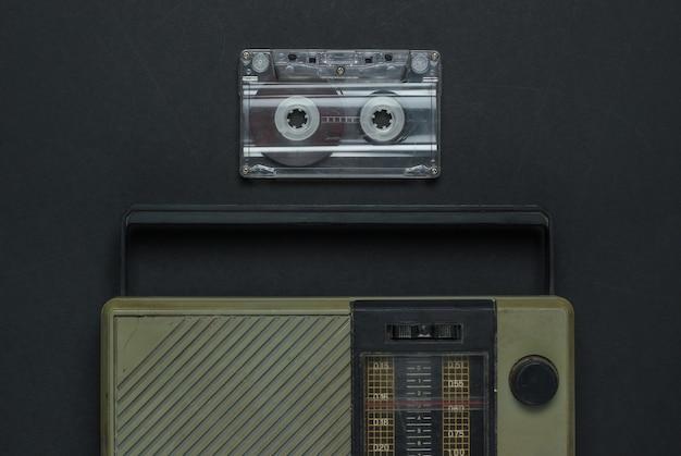 Medios retro. receptor de radio, casete de audio sobre fondo negro. vista superior.