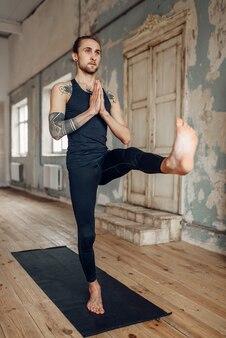 Meditación en el estudio de yogui, concentración total. yoga con tatuaje haciendo ejercicio de equilibrio sobre colchoneta en gimnasio con interior grunge.