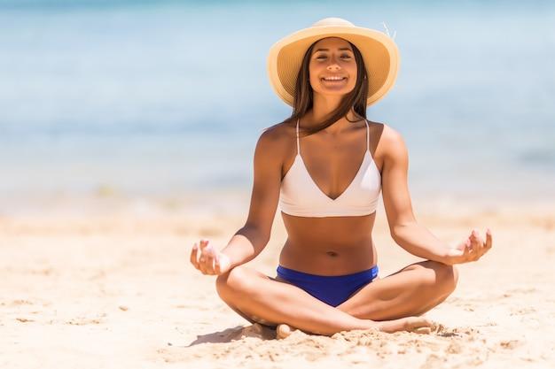 Meditación joven hermosa mujer en la playa cerca del mar