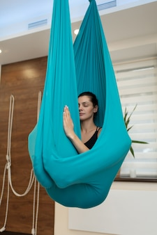 Meditación de mujer en hamaca. volar ejercicios de estiramiento de yoga en el gimnasio