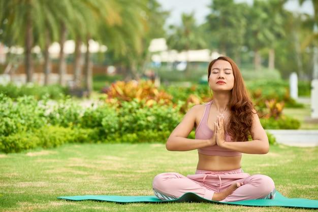 Meditando mujer étnica en pradera