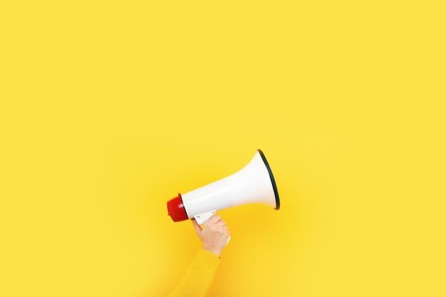 Megáfono en mano sobre un fondo amarillo