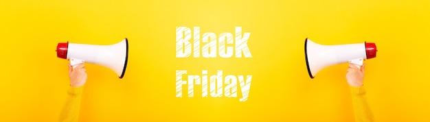Megáfonos en manos e inscripción viernes negro sobre fondo amarillo, imagen panorámica, concepto de ventas