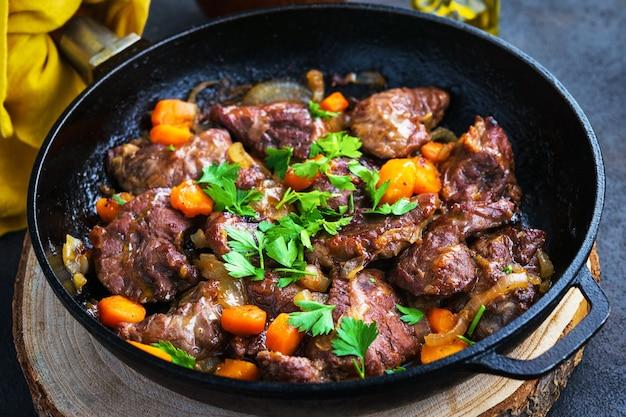 Mejillas de cerdo guisadas con verduras en una sartén de hierro, pan rebanado, aceite de oliva, sobre un fondo oscuro