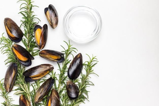 Mejillones al romero en mesa. agua en un recipiente de vidrio. endecha plana
