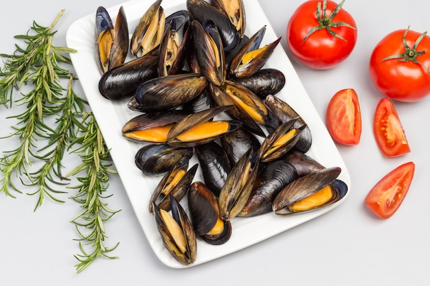 Mejillones con conchas abiertas en un plato blanco. romero y tomates en mesa. endecha plana.