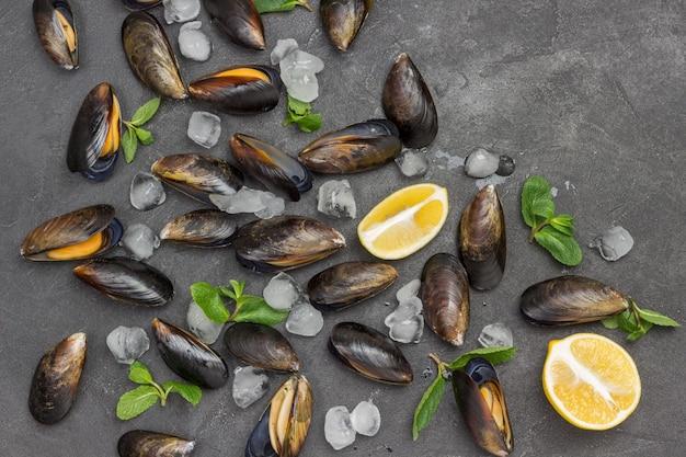 Mejillones con limón y hielo, menta se esparcen sobre la mesa. mariscos mariscos. endecha plana