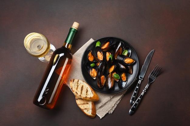 Mejillones de marisco y hojas de albahaca en un plato negro con botella de vino, copa de vino, rebanadas de pan, tenedor, cuchillo, arpillera sobre fondo oxidado. vista superior.