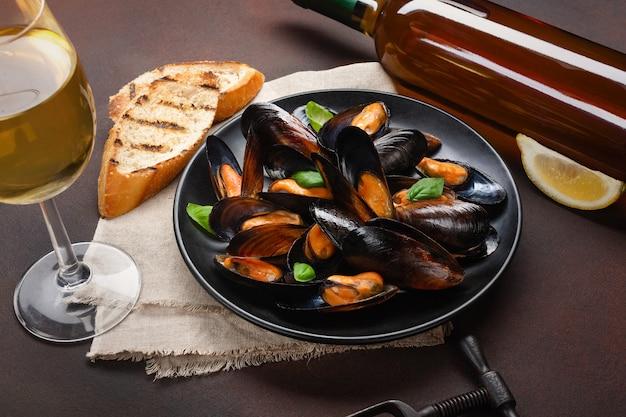 Mejillones de marisco y hojas de albahaca en un plato negro con botella de vino, copa de vino, sacacorchos, rebanadas de pan, arpillera sobre fondo oxidado. vista superior.