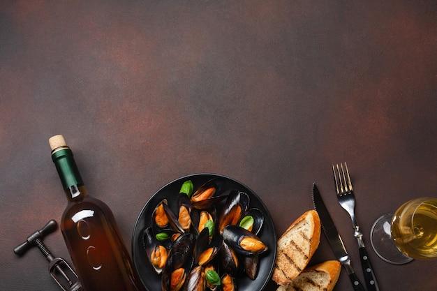 Mejillones de marisco y hojas de albahaca en un plato negro con botella de vino, copa de vino, sacacorchos, rebanadas de pan, tenedor y cuchillo sobre fondo oxidado. vista superior con lugar para su texto.