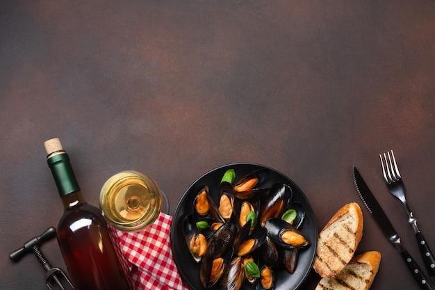 Mejillones de marisco y hojas de albahaca en un plato negro con botella de vino, copa de vino, sacacorchos, tenedor y cuchillo sobre una toalla y fondo oxidado. vista superior con lugar para su texto.