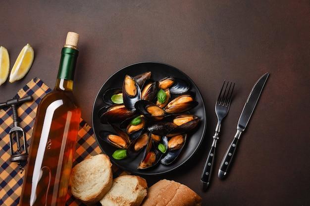 Mejillones de marisco y hojas de albahaca en un plato negro con botella de vino, sacacorchos, rebanada de pan, tenedor y cuchillo sobre una toalla y fondo oxidado. vista superior con lugar para su texto.