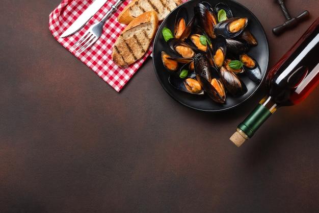 Mejillones de marisco y hojas de albahaca en un plato negro con botella de vino, sacacorchos, tenedor y cuchillo sobre una toalla y fondo oxidado. vista superior con lugar para su texto.