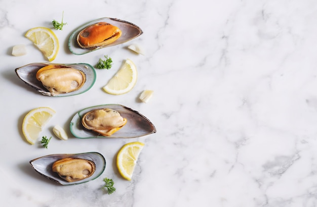 Mejillones de nueva zelanda con rodajas de limón, perejil y ajo, sobre textura de mármol blanco