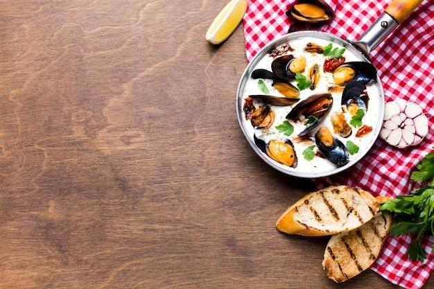 Mejillones planos en salsa blanca sobre mantel con copyspace