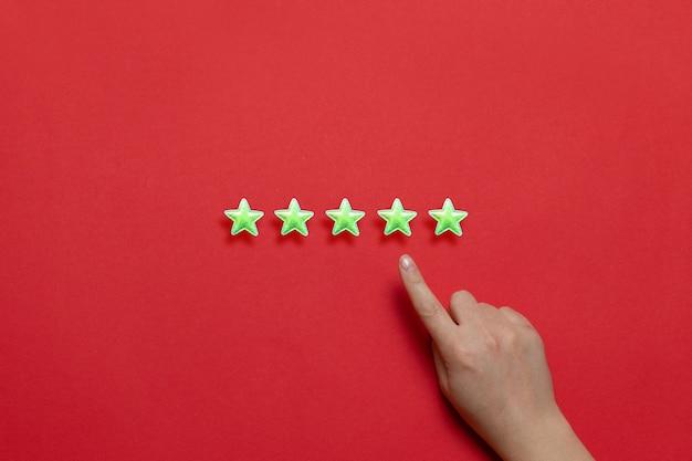 La mejor calificación de la prestación de servicios. estrellas amarillas brillantes y una mano femenina con un dedo índice sobre un fondo rojo.