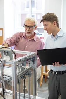 Mejor colaboración. hombre mayor encantador que cambia las configuraciones de la impresora 3d junto con su joven pasante mientras trabajaban juntos en la oficina